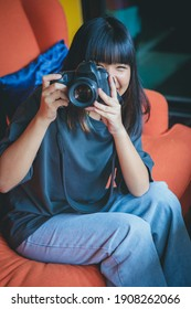 asian teenager sitting on sofa and taking a photograph by dslr camera