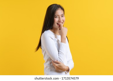 Asian teenager in white casual shirt shy isolated on yellow background in studio.