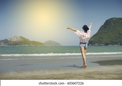Asian teenager woman has take a relaxing on beautiful beach. Rising up her hand about freshen or happy concept. happy girl. rest time at the beach. Filtered image. Selective focus
