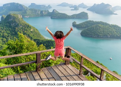 Asian teens girl travel to sea adventure holiday in Asia, Woman happy jumping on viewpoint mountain nature landscape Koh Wua Ta Lap island ocean in Mu Ko Ang Thong, Surat Thani, vacation in Thailand