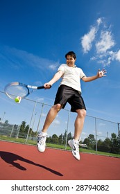 An asian tennis player jumping in the air hitting tennis ball