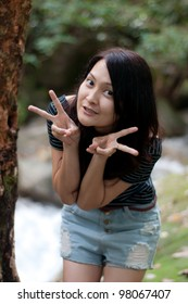 asian thai attractive woman standing at tree in waterfall