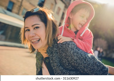 Asian Thai aunt plays with her 5 year old mixed race Asian Caucasian Australian nephew in the city. Filtered color shift, and sun flare effects.