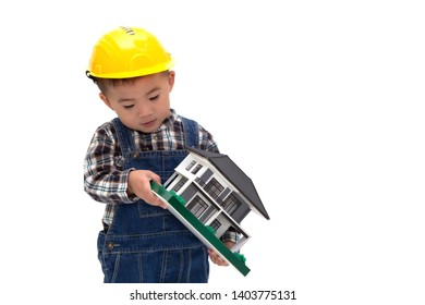Asian Thai baby boy wearing an engineer suit with hard hat and holding a sample house isolated on white background, Construction worker of real estate concept, One year six month old