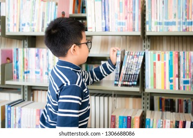 Asian Thai boy wearing glasses, long sleeves and shorts. He is choosing and picking up books on the bookshelf. in the library at school. In Bangkok, Thailand.