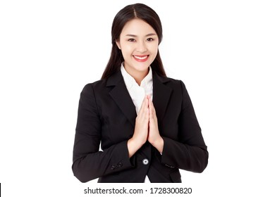 Asian Thai businesswoman wearing a black suit made a hello gesture calls Sawasdee or Was with a smiley face. Thai culture is  friendly greeting. studio head shot isolated.