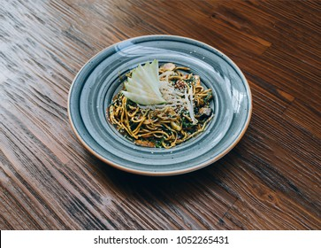Asian, thai, chinese or japanese vegetable noodles on the wooden table surface. Green Noodles on wood table from top view. Traditional Asian or thai restaurant interior.