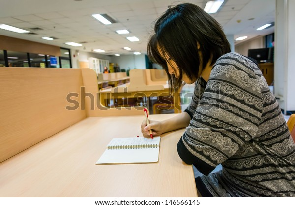 Asian Thai college girl student is writing her diary note book or doing education research study on a clean desk in the library university