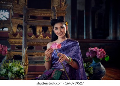Asian thai girl in traditional costume.Beautiful woman wearing thai dress style.Female sitting and make flower garlands (thai Culture) in temple ,she smiling and happy at Ayutthaya province,Thailand.