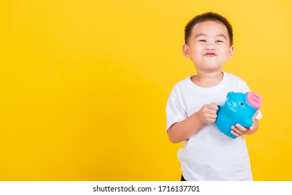 Asian Thai happy portrait cute little cheerful child boy smile putting coin money to the piggy bank and looking camera, studio shot isolated on yellow background with copy space
