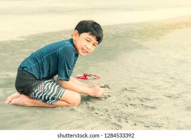 Asian thai kid playing on the beach
