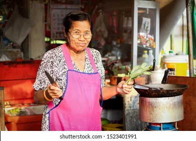 Asian thai local street food vendor woman avoid sunlight in shade and cooking for sale. Old female wear glasses aprons with sunset and blurred small carte restaurant in local housing estate background