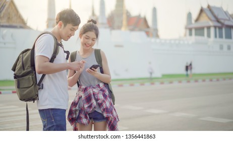 Asian Thai pretty couple using smartphone while travel in Bangkok Thailand