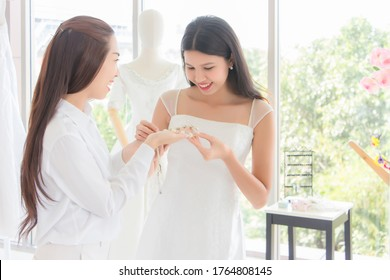 An Asian Thai woman is trying on a wedding dress with a smiling face. The owner of the rental store brought accessories to try them out willingly and looked after the customers with attention.