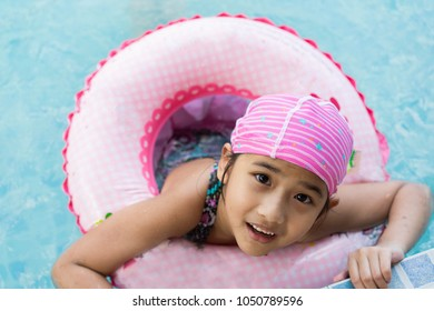 Asian Thailand Kids cute little girl Wearing rubber ring Swim in the pool