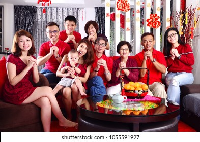 """Asian three generations celebrating chinese new year. Chinese characters in the photo means """"wealthy and prosperous"""""""