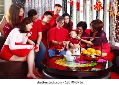 "Asian three generations family celebrating chinese new year. Grandfather giving red packet to his youngest grandchild. Chinese characters in the photo means ""wealthy and prosperous"""