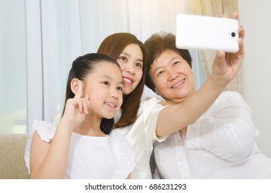 Asian three generations family taking selfie with smartphone