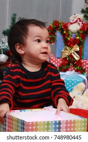 Asian toddler boy handle colorful Christmas present box and try to open up.Boy playing around while his family decorate the Christmas tree.Happy family concept.Selective focus.
