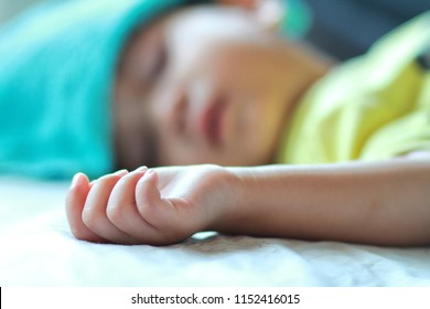 ็Hand of Asian toddler boy lie down on the bed,boy get sick,he has got high fever and sleeping on parent bed. He has wet blue towel on his forehead to relief the temperature.Selective focus