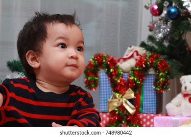 Asian toddler boy playing with Christmas stuff while his family decorate the Christmas tree.Happy family concept.Selective focus.
