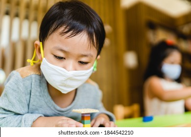 Asian toddler boy playing toy block in day care school.3.5 years old boy child wearing face mask in Day care.Covid-19 coronavirus.Nursery.Social distancing in school kid.Back to school.New normal. - Shutterstock ID 1844542210