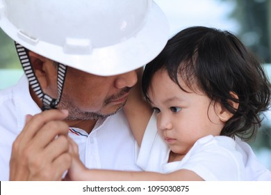 Asian toddler boy try to fasten his father's engineering Helmet.Concept of father and son.White color tone.