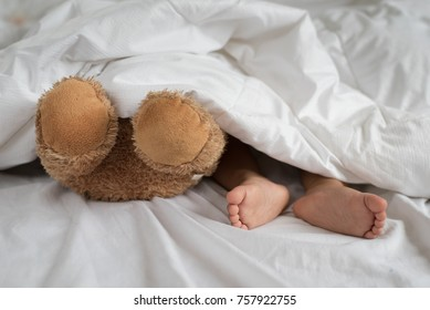 asian toddler feet beside teddy bear feet in white bed, sheet and pillow - toddler sleeping with teddy bear
