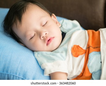 Asian toddler fell into a slumber on bed.