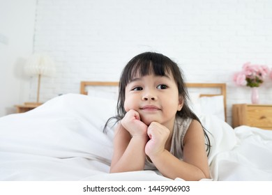 An asian toddler girl 3 years old lie on her stomach in bed and rest her chin on hands