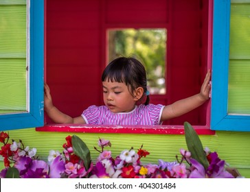 Asian toddler girl open window with two hands