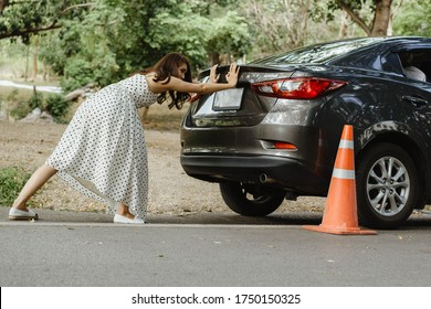 An Asian tourist girl in a white dress pushes her car by herself The cause is due to her car crashing without knowing the cause. Car insurance concept