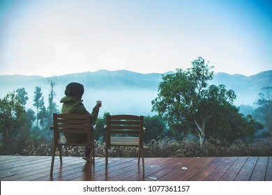 Asian tourist sitting in a chair watching morning misty view of mountain sipping a cup of coffee