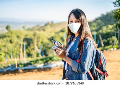 Asian tourist traveler to another country city wearing face mask of COVID-19 health and safety pandemic in an adventure traveling on the mountains, camera taking a photograph of the misty mountain - Shutterstock ID 1879105348
