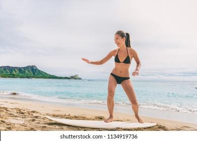 Asian tourist woman on Hawaii beach learning to surf at surfing school in Waikiki, Honolulu, Oahu. Girl having fun practicing on surfboard on shore.