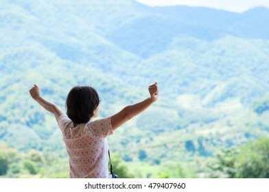 Asian tourist woman standing at balcony and looking on the landscape. Rear view.  Raised up hands. Relaxations, Happiness, Freedom.