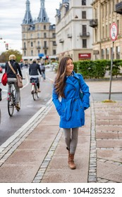 Asian tourist woman walking in Copenhagen city street next to bike path, modern commute. Urban living lifestyle young happy person commuting in fall or spring.