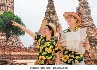 Asian tourists with colorful floral shirts using paper map to find attraction in old temple ruins. Couple go sightseeing in Wat Chaiwatthanaram, Ayutthaya Historical Park, Thailand, Southeast Asia.