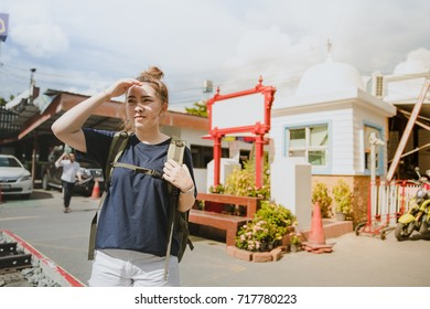 Asian tourists woman looking friend at Tourist Attraction wait time friend arrived at girl stand up