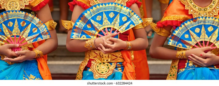 Asian travel background. Group of beautiful Balinese dancer women in traditional Sarong costumes with fans in hands dancing Legong dance. Arts, culture of Indonesian people, Bali island festivals. - Shutterstock ID 632284424