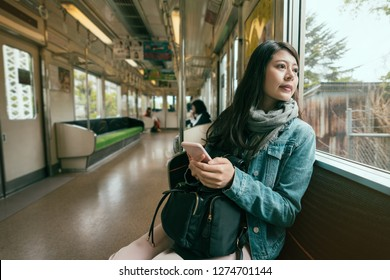 asian travel woman inside subway train looking out beautiful view from window. young girl holding smart phone sitting on seat in metro. fashion chinese woman commute in tour trip wear scarf spring