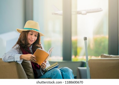 Asian traveler with carry on luggage in international airport reading a book while waiting for her flight.