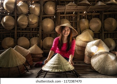 Asian traveler female craftsman making the traditional vietnam hat in the old traditional house in Ap Thoi Phuoc village, Hochiminh city, Vietnam, traditional artist concept