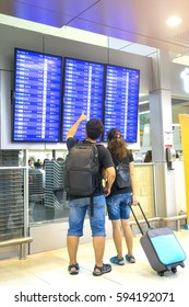 Asian traveler looking flight information screen board in airpor