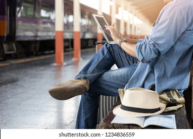Asian traveler man use tablet to buy train ticket online at train station