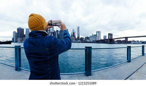Asian traveler taking photo with mobile phone in Brooklyn bridge at sunset. New York city.