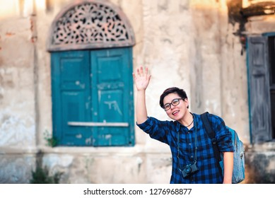 Asian Traveler wearing Blue Plaid Shirt Raise Hand Up to Say Hi with Friends and Carrying Backpack and Camera for Travelling in Bangkok , Thailand in Relax Emotion Lifestyle Travel Moment in Holiday
