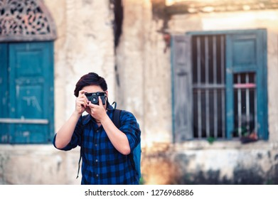 Asian Traveler wearing Blue Plaid Shirt Taking a Photo with Film Camera for Travelling in Bangkok , Thailand in Relax Emotion Lifestyle Travel Moment in Hollidays