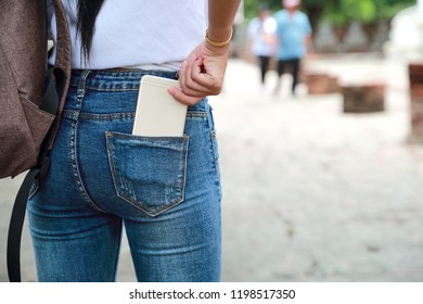 asian traveler woman in ancient temple with backpack and holding cell phone in pocket jean