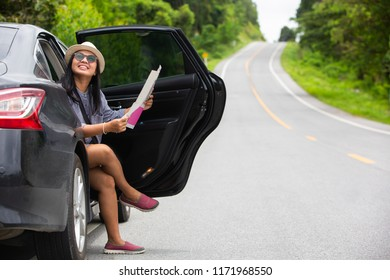 Asian traveler woman using mobilephone and map beside car at hill road . Travel concept